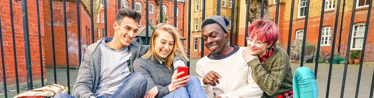 Multicultural group of four people sitting in front of the fence of a building on the street, laughing and watching at a smartphone.